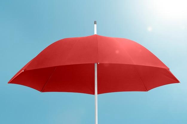 Roter regenschirm mit kopienraum am blauen himmel