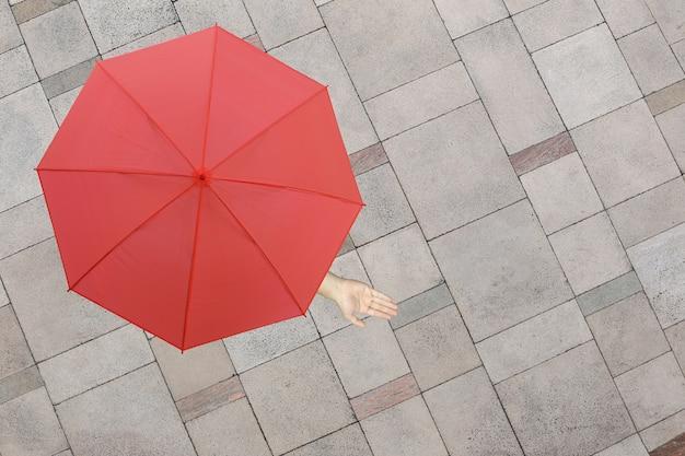 Roter regenschirm und eine hand des mannes stehend auf dem steinboden und hand, die draußen hervorstehen.
