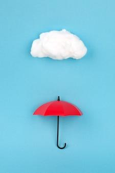Roter regenschirm unter der wolke auf himmelblau