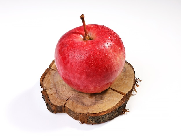 Roter reifer apfel mit wassertropfen auf kreisapfelbaumstumpf