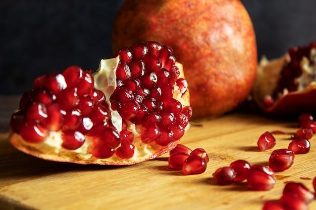 Roter reifer granatapfel, in einem dramatischen stil, auf einem dunklen hintergrund, auf einer tafel, stillleben
