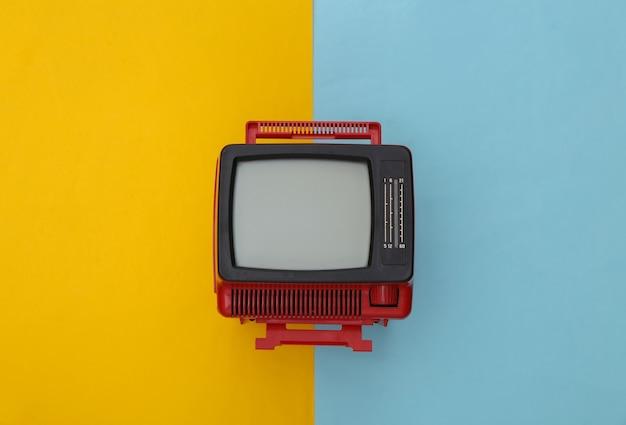 Roter retro- alter mini-fernseher auf gelb-blauem pastellhintergrund. ansicht von oben