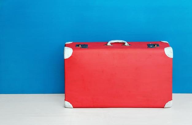 Roter retro-koffer an der blauen wand. reisen und abenteuer.