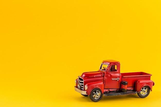 Roter retro- spielzeuglastwagen auf gelbem hintergrund.