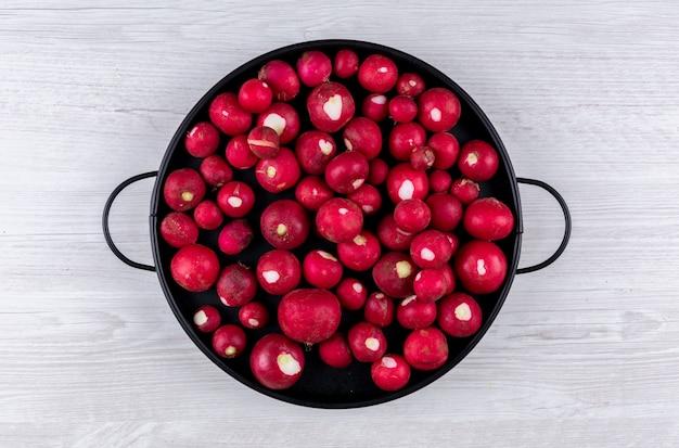 Roter rettich in einer schwarzen pfanne auf weißem holztisch. flach liegen.