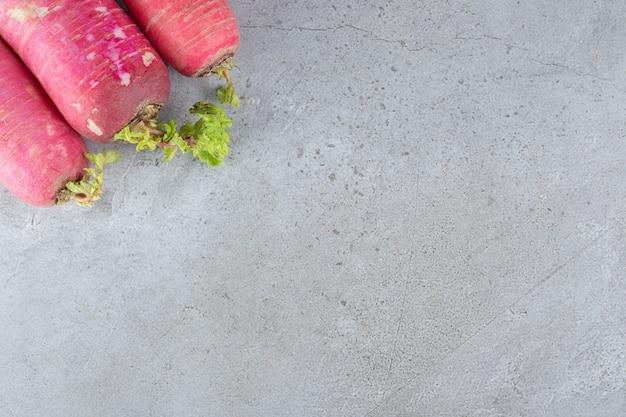 Roter rettich und blätter auf grauem hintergrund. foto in hoher qualität