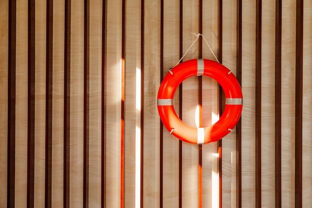 Roter rettungsring, der an der hölzernen wand eines hafengebäudes hängt