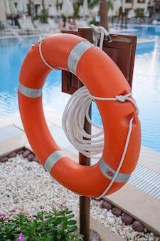 Roter rettungsring und seile, um leben zu retten, wenn menschen in der nähe des pools ertränkt werden. foto in hoher qualität