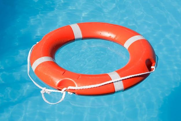 Roter rettungsschwimmer auf blauem wasser