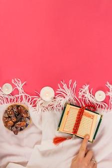 Roter rosenkranz; beleuchtung kerze; heiliges buch von koran und termine in der schüssel auf schal über rotem hintergrund