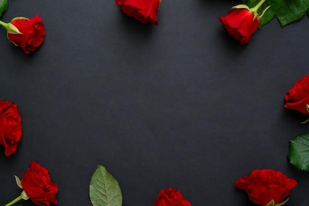 Roter rosenrahmen auf schwarzem hintergrund, kopierraum.