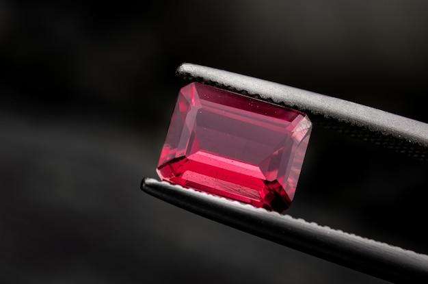 Roter rubinroter edelstein mit dunklem schwarzgrund.