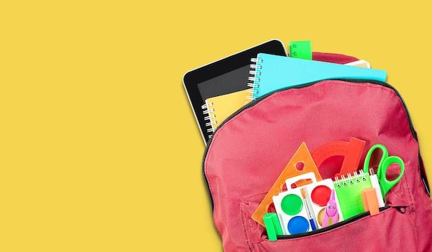 Roter rucksack mit schulmaterial auf gelbem hintergrund