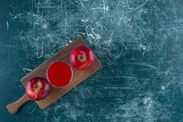 Roter saft und apfel auf dem brett, auf blauem hintergrund. foto in hoher qualität