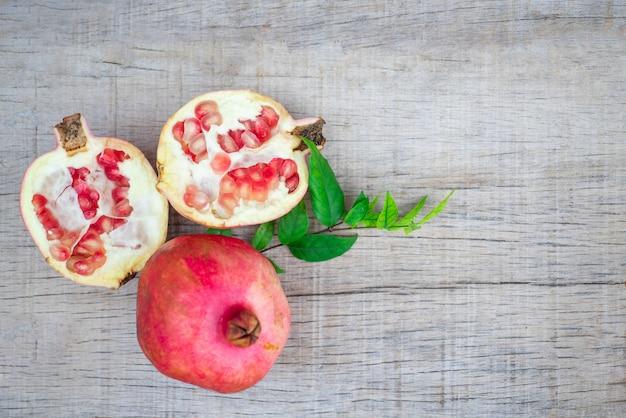 Roter saftgranatapfel auf dunklem hölzernem hintergrund