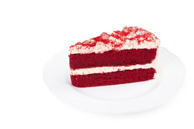 Roter samt-kuchen geschnitten im stück auf weißer platte auf weißem hintergrund