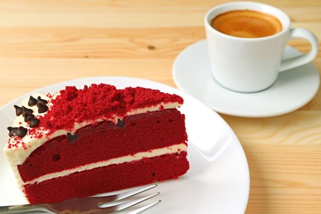 Roter samt-shortcake mit frischkäse-bereifen und eine schale heißer kaffee im hintergrund