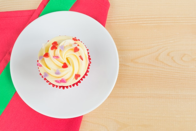 Roter samtkleiner kuchen mit grünem weihnachtsband auf hölzernem brett