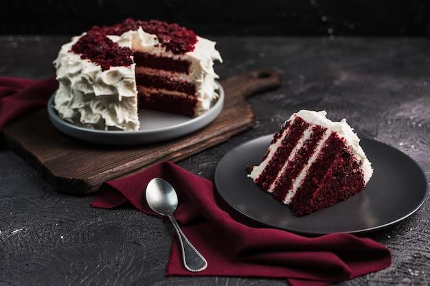 Roter samtkuchen auf dunklem hintergrund, seitenansicht der nahaufnahme. süßes dessert für den urlaub.
