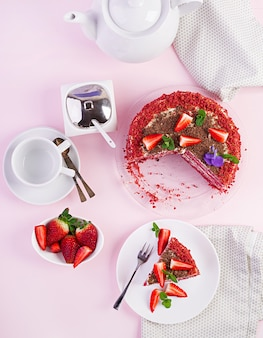 Roter samtkuchen auf rosa. tee trinken. sitzordnung bei tisch.