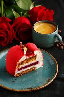 Roter samtkuchen auf teller mit tasse kaffee und roter rose.