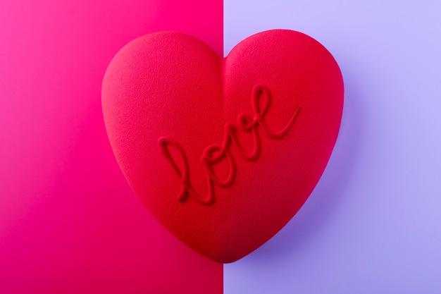 Roter samtkuchen in herzform mit der aufschrift liebe auf rosa und blauem hintergrund