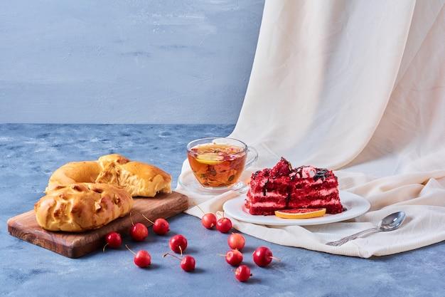 Roter samtkuchen mit brötchen und tee auf einem holzbrett auf blau