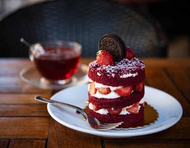 Roter samtkuchen mit erdbeer-schokoladen-keks auf dem braunen holztisch in einem café