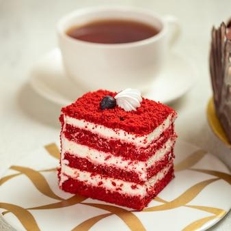Roter samtkuchen mit tasse tee, kuchenscheibe hautnah