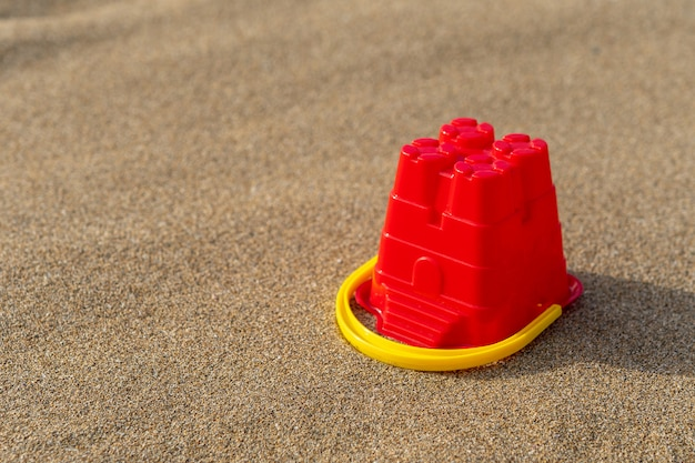 Roter sandburgschaufel auf sandhintergrund
