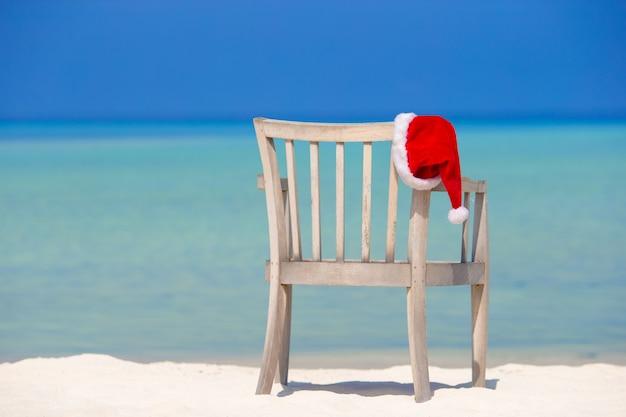 Roter sankt-hut auf strandstuhl an den tropischen ferien