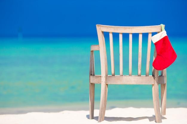 Roter sankt-hut auf stuhl am tropischen weißen strand