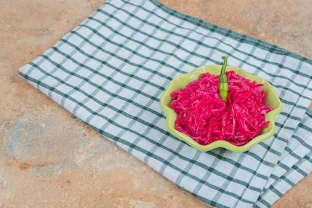 Roter sauerkrautsalat in grüner schüssel mit tischdecke