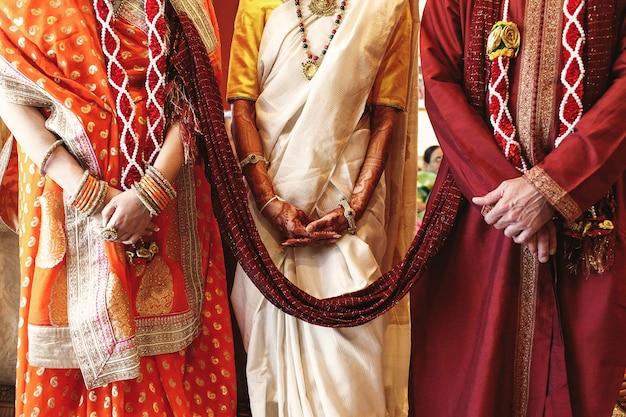 Roter schal schließt die brauteltern an, die für indische hochzeit gekleidet werden