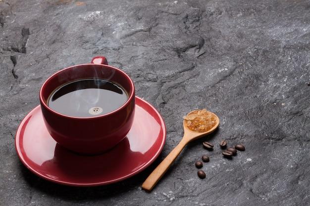 Roter schalenkaffee und -zucker im löffel auf felsen