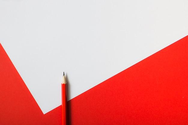 Roter scharfer bleistift auf doppeltem weißem und rotem papierhintergrund
