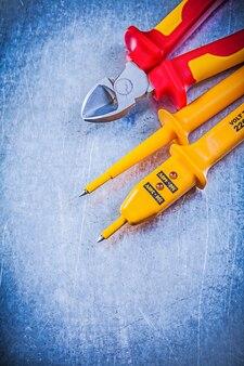 Roter scharfer drahtschneider des gelben elektrischen testers auf elektrischem hintergrundelektrizitätskonzept