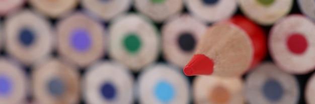 Roter scharfer hölzerner bleistift, der näherer mehrfarbiger stumpfer nahaufnahmehintergrund liegt. führungskompetenzkonzept