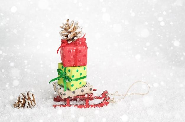 Roter schlitten, der weihnachts- oder neujahrsgeschenke auf schneeweißem hintergrund liefert.