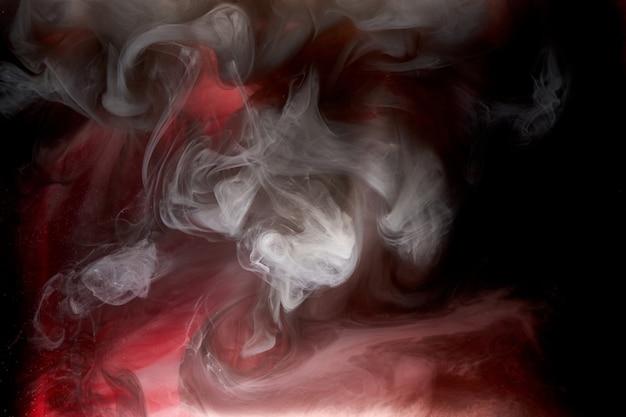 Roter schwarzer pigment wirbelnder tintenabstrakter hintergrund, flüssige rauchfarbe unter wasser