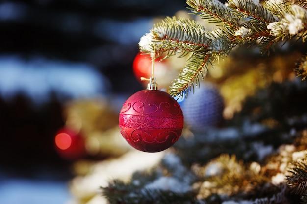 Roter spielzeugball auf dem weihnachtsbaum im wald des verschneiten winters
