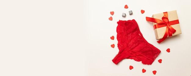 Roter spitzenhöschen mit einer überraschungs-geschenkbox in kraftpapier eingewickelt