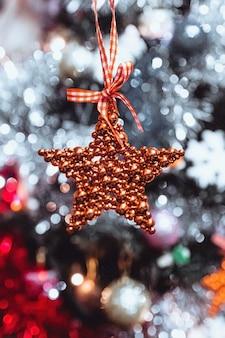 Roter stern, der auf dem hintergrund des weihnachtsbaumes hängt