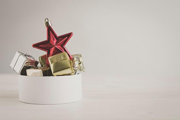 Roter stern mit weihnachtsgeschenken auf unscharfem hintergrund
