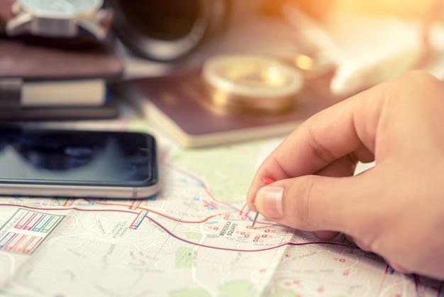 Roter stift auf einer weltkarte. reiseplanung