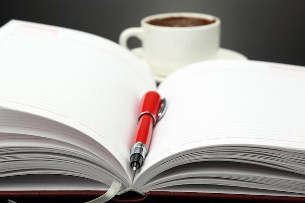 Roter stift, der auf einem offenen notizbuch auf der tasse mit schwarzem kaffee liegt