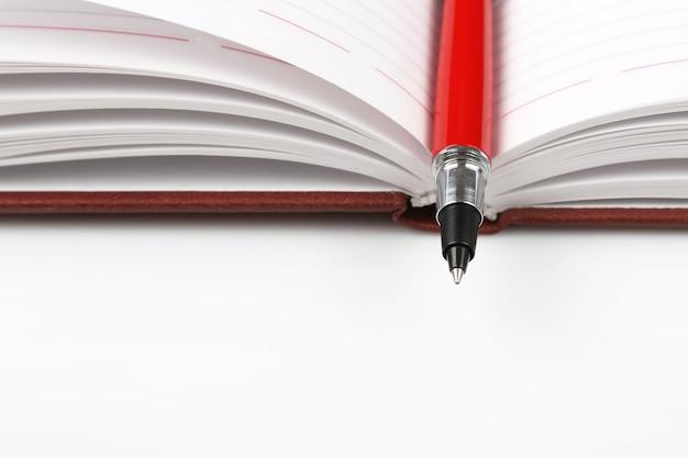 Roter stift, der auf einem offenen notizbuch liegt