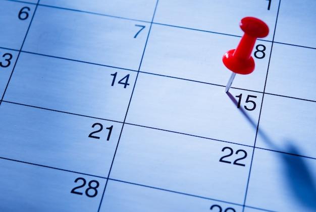 Roter stift, der das 15. auf einem kalender markiert