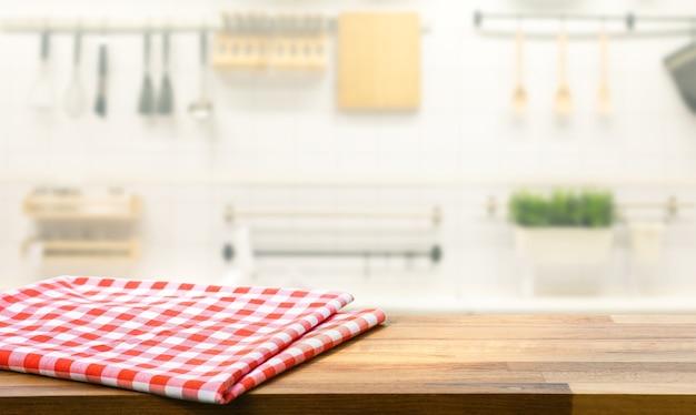 Roter stoff, stoff auf holztischplatte auf verschwommener küchentheke
