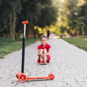 Roter stoßroller vor dem mädchen, das auf gehweg im park sitzt